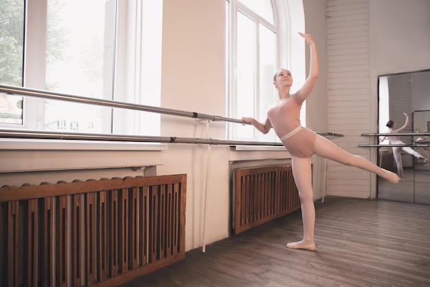 Junge anmutige balletttänzerin, die im trainingsstudio tanzt. schönheit des klassischen balletts. mädchen, das vor dem fenster im klassenzimmer durchführt. pastellfarben, bewegungsbegriff, bewegung, kindheit.