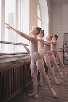 Junge anmutige weibliche balletttänzer tanzen im trainingsstudio. schönheit des klassischen balletts. mädchen, die vor dem fenster im klassenzimmer auftreten. pastellfarben, bewegungsbegriff, bewegung, kindheit.