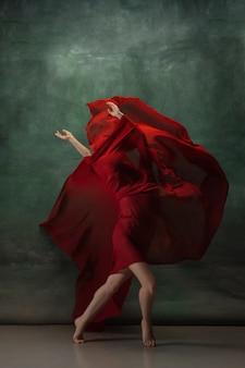 Junge anmutige zarte ballerina auf dunkelgrünem studioraum mit rotem stoff