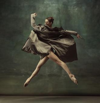 Junge anmutige zarte ballerina auf dunklem studio