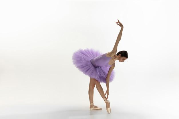 Junge anmutige zarte ballerina auf weißer wand