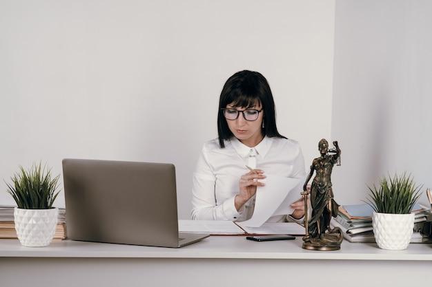 Junge anwältin, die in ihrem büro oder aus der ferne arbeitet.