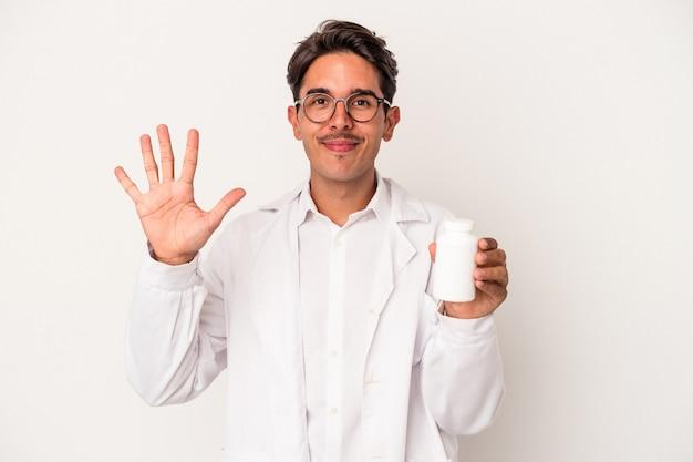 Junge apotheker gemischte rasse mann hält pillen isoliert auf weißem hintergrund lächelnd fröhlich zeigt nummer fünf mit den fingern.