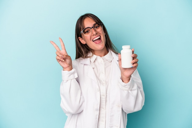 Junge apothekerfrau, die pillen einzeln auf blauem hintergrund hält, fröhlich und sorglos, die ein friedenssymbol mit den fingern zeigen.