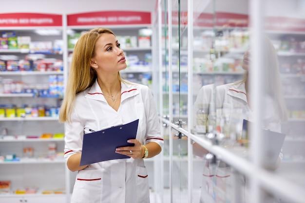 Junge apothekerin auf der suche nach medikamenten in apothekenregalen