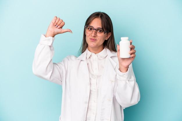 Junge apothekerin, die pillen einzeln auf blauem hintergrund hält, fühlt sich stolz und selbstbewusst, beispiel zu folgen.