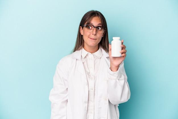Junge apothekerin, die pillen einzeln auf blauem hintergrund hält, verwirrt, fühlt sich zweifelhaft und unsicher.