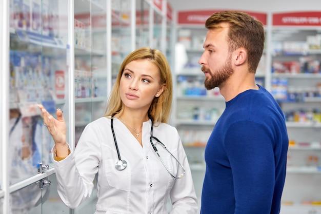 Junge apothekerin hilft kranken männlichen kunden bei der auswahl verschreibungspflichtiger medikamente