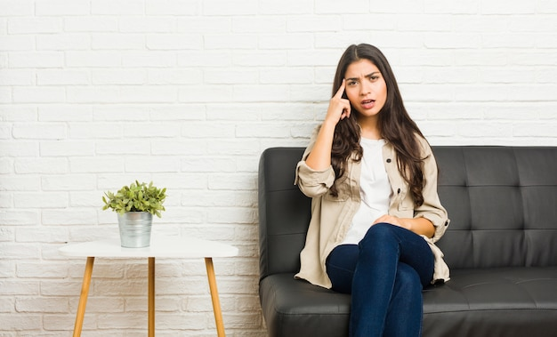 Junge arabische frau, die auf dem sofa zeigt eine enttäuschungsgeste mit dem zeigefinger sitzt.