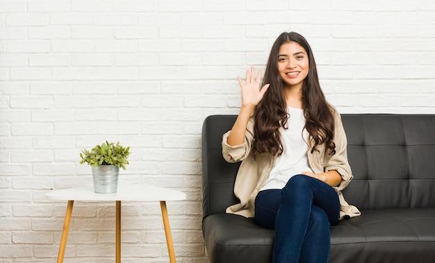 Junge arabische frau, die auf dem sofalächeln nett sitzt, nr. fünf mit den fingern zeigend.