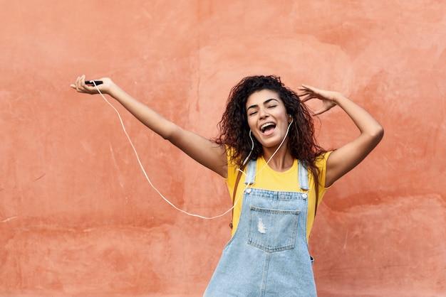 Junge arabische frau, die draußen musik mit kopfhörern hört