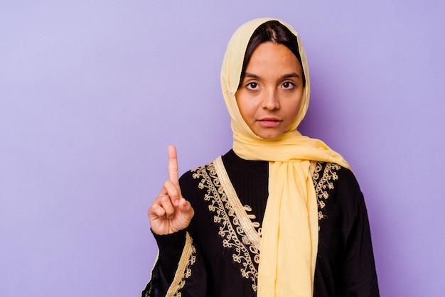 Junge arabische frau, die ein typisches arabisches kostüm trägt, das auf purpurrotem hintergrund isoliert ist und die nummer eins mit dem finger zeigt.