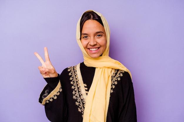 Junge arabische frau, die ein typisches arabisches kostüm trägt, das auf violettem hintergrund isoliert ist und die nummer zwei mit den fingern zeigt.