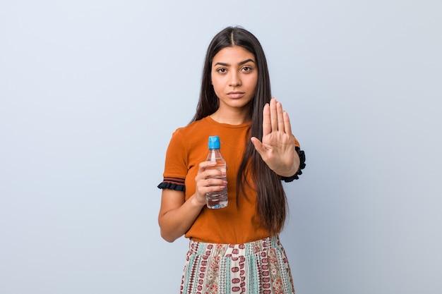Junge arabische frau, die eine wasserflasche hält, die mit ausgestreckter hand steht und stoppschild zeigt, das sie verhindert.