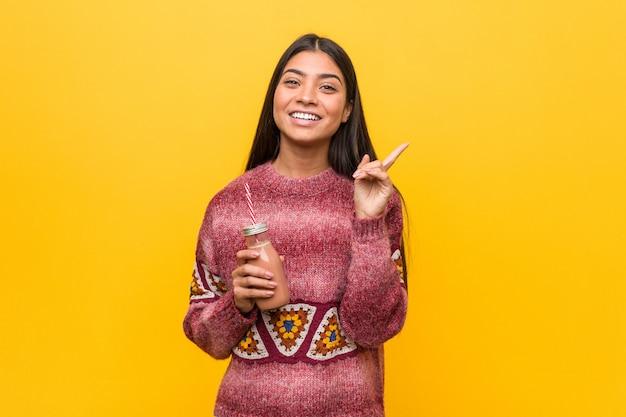 Junge arabische frau, die einen smoothie lächelt hält, freundlich zeigend mit dem zeigefinger weg.
