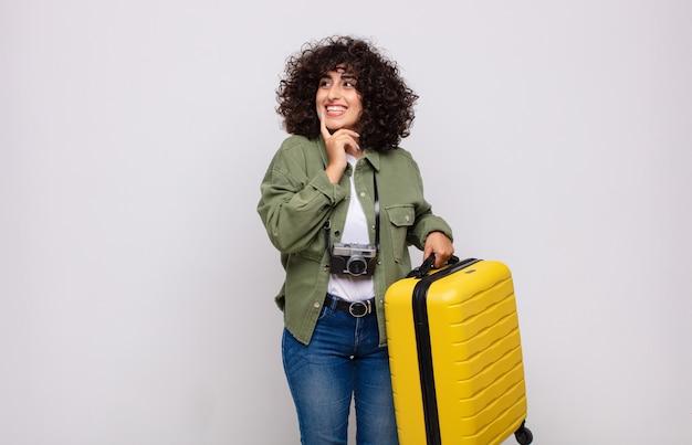 Junge arabische frau, die glücklich lächelt und tagträumen oder zweifel hat und auf das seitenreisekonzept schaut