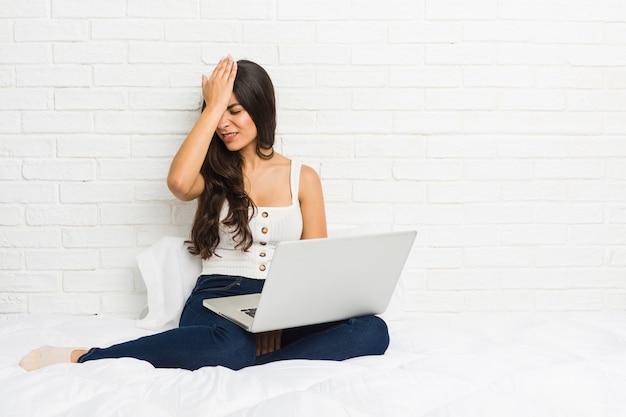 Junge arabische frau, die mit ihrem laptop auf dem bett etwas vergisst, stirn mit palme schlägt und augen schließt.