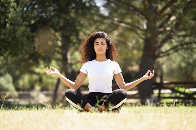 Junge arabische frau, die yoga in der natur tut