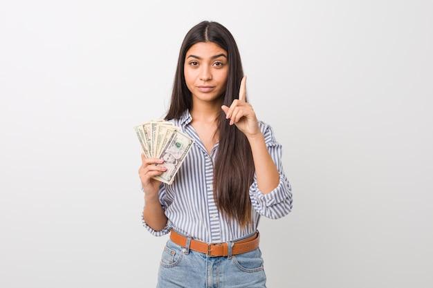 Junge arabische frau hält dollar, der nummer eins mit finger zeigt.