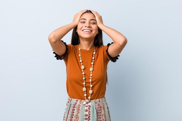 Junge arabische frau lacht freudig und hält hände auf dem kopf. glückskonzept.