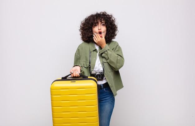 Junge arabische frau mit mund und augen weit offen und hand auf kinn, sich unangenehm geschockt, sagend was oder wow reisekonzept