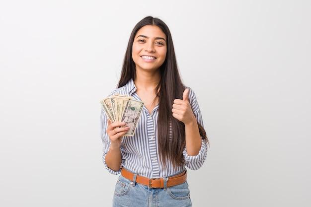 Junge arabische frau, welche die dollar lächeln und den daumen hochheben hält