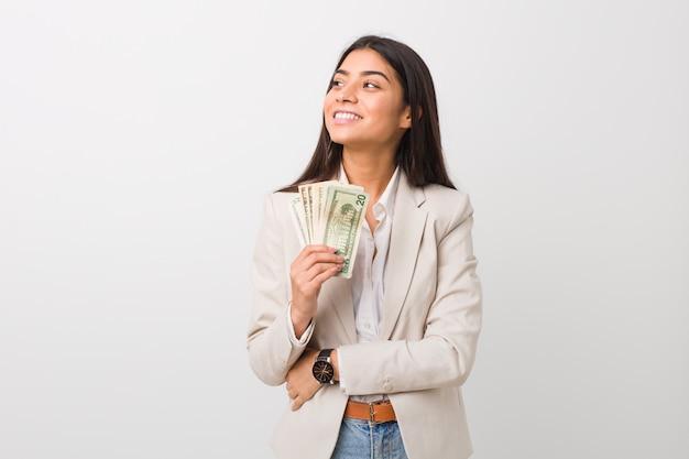Junge arabische geschäftsfrau, die dollars hält, die mit verschränkten armen zuversichtlich lächeln.