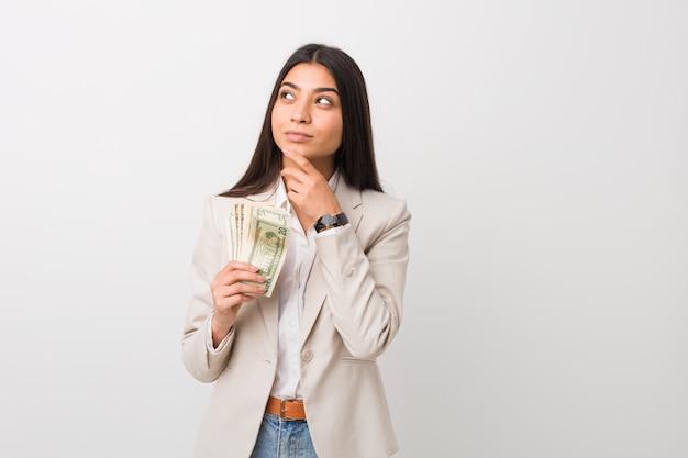 Junge arabische geschäftsfrau, die dollars hält, die mit zweifelhaftem und skeptischem ausdruck seitwärts schauen.