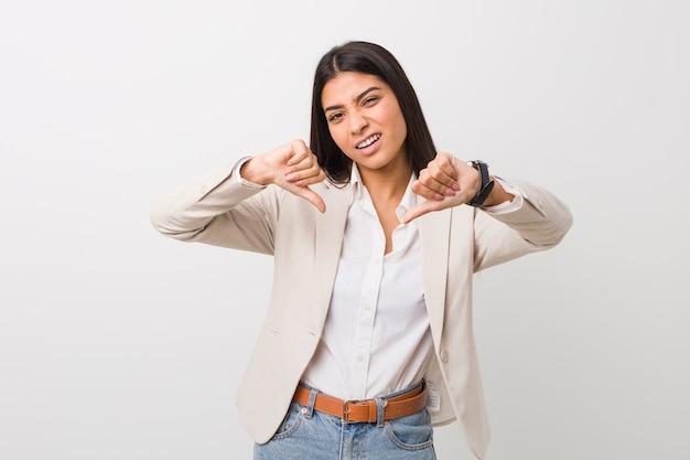 Junge arabische geschäftsfrau, die unten daumen zeigt und abneigung ausdrückt.
