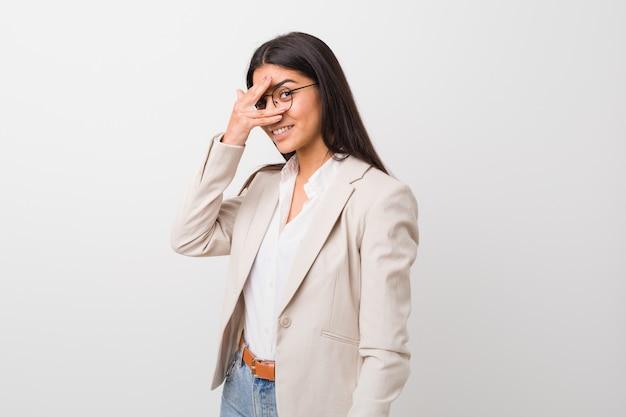 Junge arabische geschäftsfrau lokalisiert gegen einen weißen wandblinzeln an der kamera durch finger, verlegenes bedeckungsgesicht.