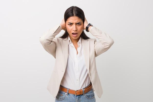 Junge arabische geschäftsfrau lokalisierte weiße bedeckungsohren mit den händen, die versuchen, nicht zu lauten ton zu hören.
