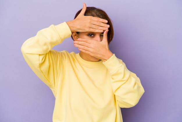 Junge arabische mischlingsfrau blinzelt durch finger, verlegenes bedeckendes gesicht.