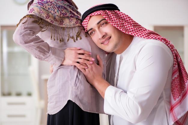 Junge arabische moslemische familie mit der schwangeren frau, die baby erwartet
