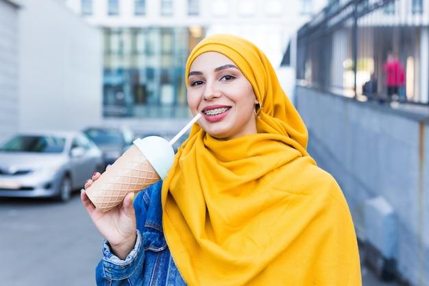 Junge arabische muslimische frau, die cocktail im freien genießt.