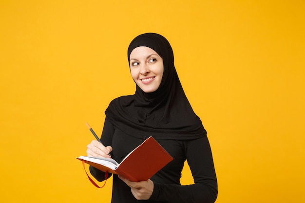 Junge arabische muslimische frau in hijab-schwarzer kleidung hält ein notizbuch, schreibt, bereitet sich auf die prüfung isoliert auf gelbem wandporträt vor. menschen religiöses lifestyle-konzept. .
