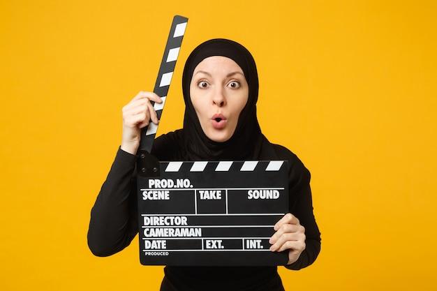 Junge arabische muslimische frau in hijab-schwarzer kleidung halten klassische schwarze filme, die clapperboard einzeln auf gelbem wandporträt machen. menschen religiöses lifestyle-konzept.