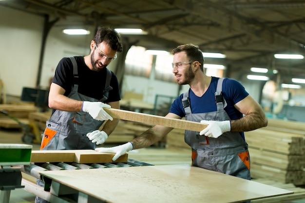 Junge arbeiter arbeiten in einer fabrik für die herstellung von möbeln