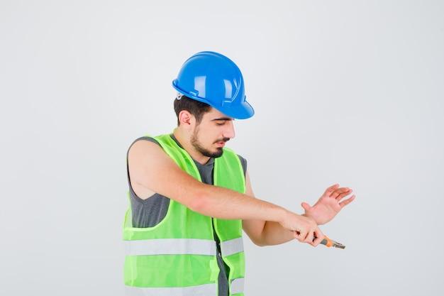 Junge arbeiter, die eine zange halten und die hand in bauuniform darauf strecken und glücklich aussehen