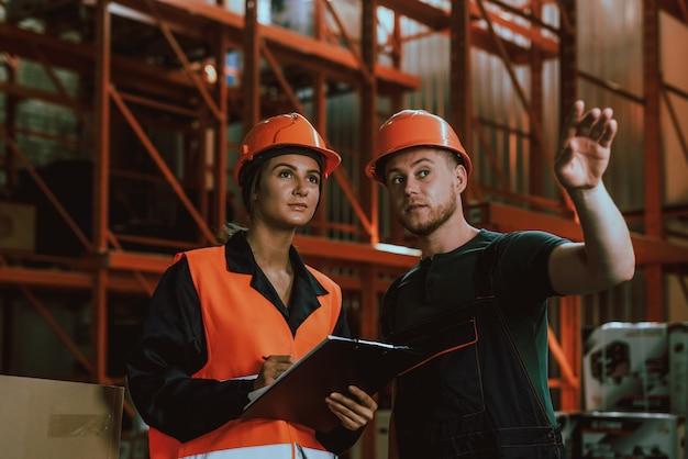 Junge arbeiter in schutzhelmen, die im lager sprechen