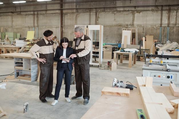 Junge arbeiterin der möbelfabrik in uniform, die weibliche manager in formeller kleidung zeigt, neue ausrüstung bei arbeitstreffen im lager?
