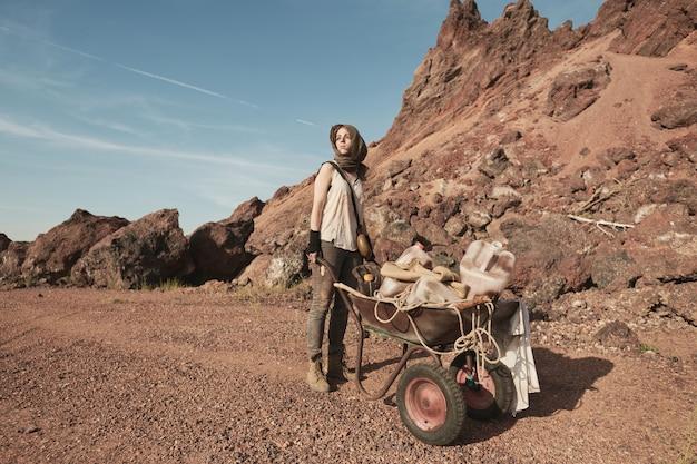 Junge arbeiterin, die mit schubkarre in der wüste und im bergbau steht
