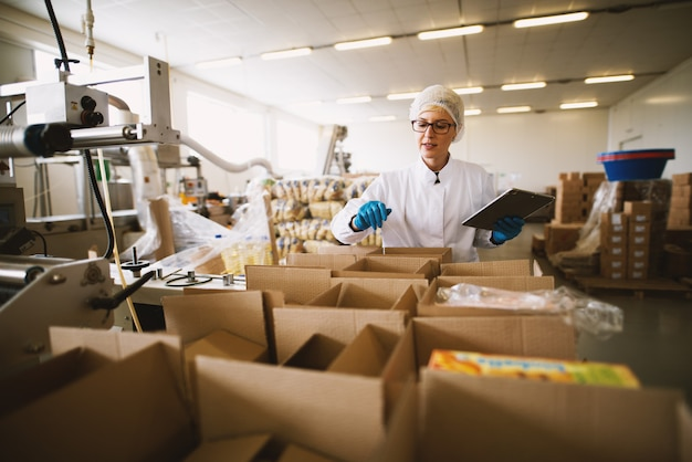 Junge arbeiterin in steriler kleidung verwendet tablette, um die richtige anzahl von paketen zu überprüfen.