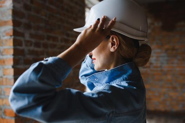 Junge arbeiterin mit weißem helm auf der baustelle.