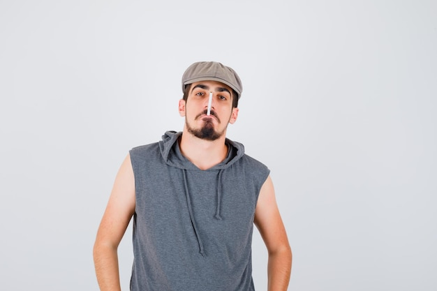 Junge arbeiterin raucht zigarette in grauem t-shirt und mütze und sieht ernst aus