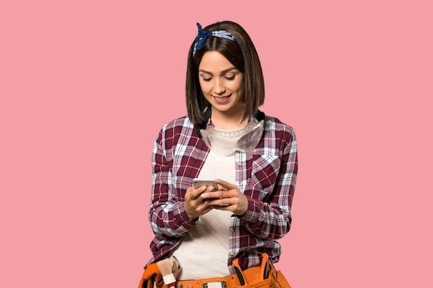 Junge arbeitnehmerfrau, die eine mitteilung mit dem mobile auf lokalisierter rosa wand sendet