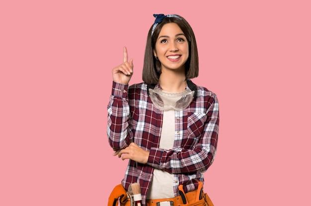 Junge arbeitnehmerfrau, die mit dem zeigefinger eine großartige idee auf lokalisierter rosa wand zeigt