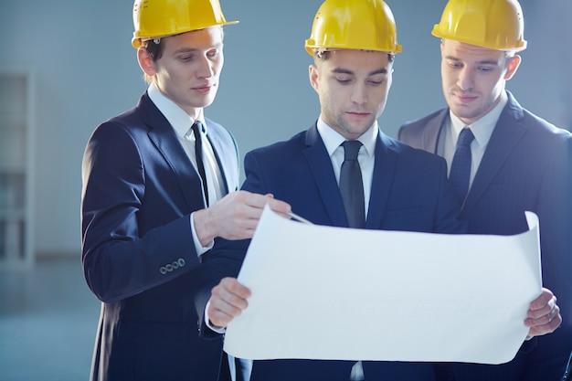 Junge architekten, die skizze des neuen gebäudes diskutieren