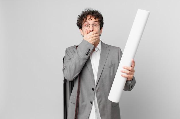 Junge architektin bedeckt den mund mit den händen mit einem schockierten