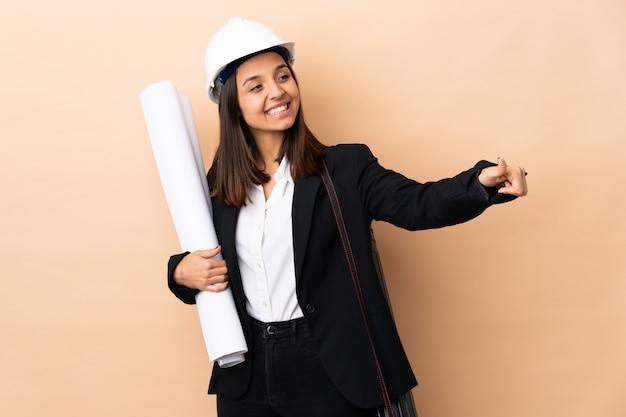 Junge architektin, die blaupausen über isoliert hält, die eine daumen hoch geste geben