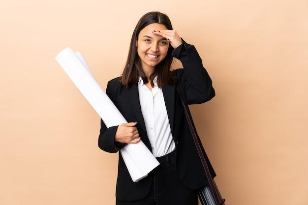 Junge architektin, die blaupausen über isolierter wand hält, die mit hand mit glücklichem ausdruck salutiert